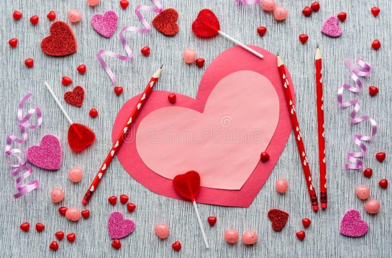 Ροζ και κόκκινη κάρτα βαλεντίνων με τα μολύβια και καραμέλα στο γκρίζο υπόβαθρο στοκ εικόνα