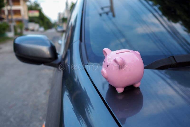 Ροζ κουμπαρά που στέκεται στο μαύρο αυτοκίνητο, εξοικονομώντας χρήματα για νέο αυτοκίνητο ή εξοικονομώντας χρήματα με ασφάλεια αυ στοκ φωτογραφίες