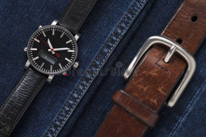Ρολόι πολυτέλειας στο ύφασμα τζιν με την καφετιά ζώνη δέρματος στοκ εικόνες