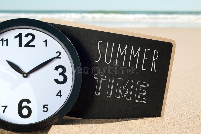 Ρολόι στο θερινό χρόνο παραλιών και κειμένων στοκ εικόνες