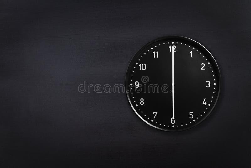 Ρολόι τοίχων που παρουσιάζει έξι η ώρα στο μαύρο υπόβαθρο πινάκων κιμωλίας Ρολόι γραφείων που παρουσιάζει 6am ή 6pm στη μαύρη σύσ στοκ φωτογραφίες