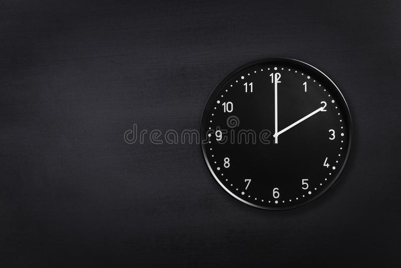 Ρολόι τοίχων που παρουσιάζει δύο η ώρα στο μαύρο υπόβαθρο πινάκων κιμωλίας Ρολόι γραφείων που παρουσιάζει 2am ή 2pm στη μαύρη σύσ στοκ εικόνες