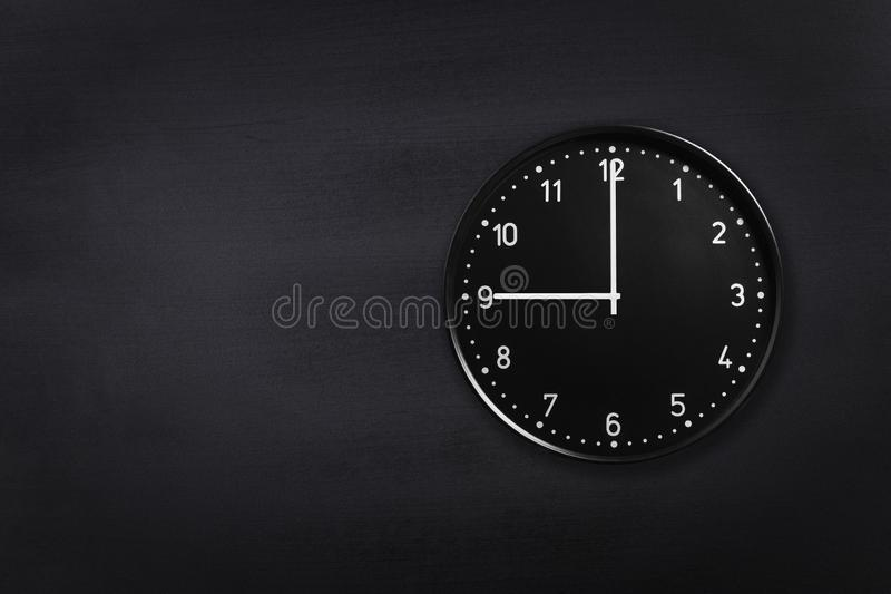 Ρολόι τοίχων που παρουσιάζει εννέα η ώρα στο μαύρο υπόβαθρο πινάκων κιμωλίας Ρολόι γραφείων που παρουσιάζει 9am ή 9pm στη μαύρη σ στοκ εικόνες με δικαίωμα ελεύθερης χρήσης