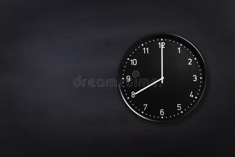 Ρολόι τοίχων που παρουσιάζει οκτώ η ώρα στο μαύρο υπόβαθρο πινάκων κιμωλίας Ρολόι γραφείων που παρουσιάζει 8am ή 8pm στη μαύρη σύ στοκ φωτογραφία με δικαίωμα ελεύθερης χρήσης