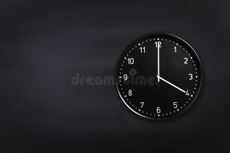 Ρολόι τοίχων που παρουσιάζει τέσσερις η ώρα στο μαύρο υπόβαθρο πινάκων κιμωλίας Ρολόι γραφείων που παρουσιάζει 4am ή 4pm στη μαύρ στοκ φωτογραφία με δικαίωμα ελεύθερης χρήσης