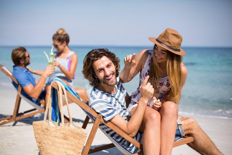 Ρομαντικά νέα ζεύγη που κάθονται στις καρέκλες γεφυρών στην παραλία στοκ φωτογραφία με δικαίωμα ελεύθερης χρήσης