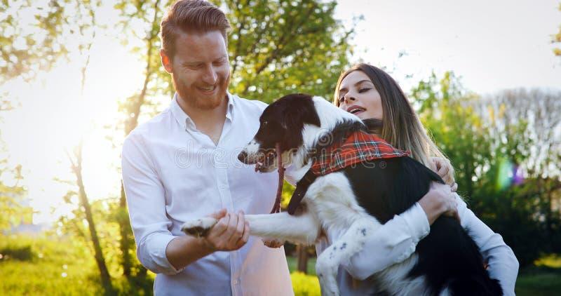 Ρομαντικά σκυλιά περπατήματος ζευγών ερωτευμένα στη φύση και χαμόγελο στοκ φωτογραφία