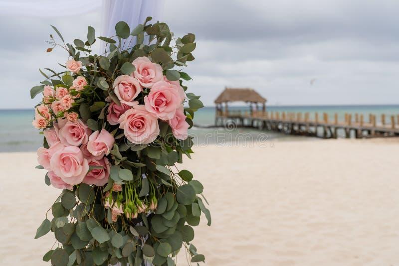 Ρομαντική διακόσμηση με τα ρόδινα τριαντάφυλλα ενός γάμου παραλιών στην παραλία με τη θάλασσα στο υπόβαθρο στοκ φωτογραφία με δικαίωμα ελεύθερης χρήσης