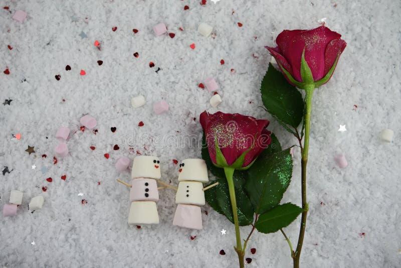 Ρομαντική εικόνα φωτογραφίας τροφίμων χειμερινής εποχής με marshmallows που διαμορφώνονται χιονάνθρωπος και κόκκινα τριαντάφυλλα  στοκ φωτογραφία
