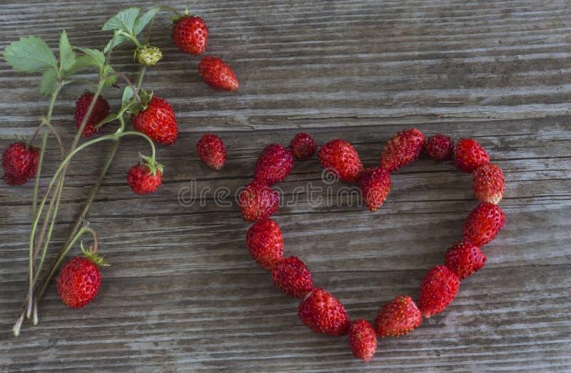 Ρομαντική καρδιά που ευθυγραμμίζεται με τις φράουλες σε ένα παλαιό ξύλινο υπόβαθρο στοκ εικόνα