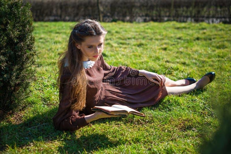 Ρομαντική νέα γυναίκα που διαβάζει ένα βιβλίο στη συνεδρίαση κήπων στη χλόη Χαλαρώστε την υπαίθρια χρονική έννοια στοκ φωτογραφίες με δικαίωμα ελεύθερης χρήσης