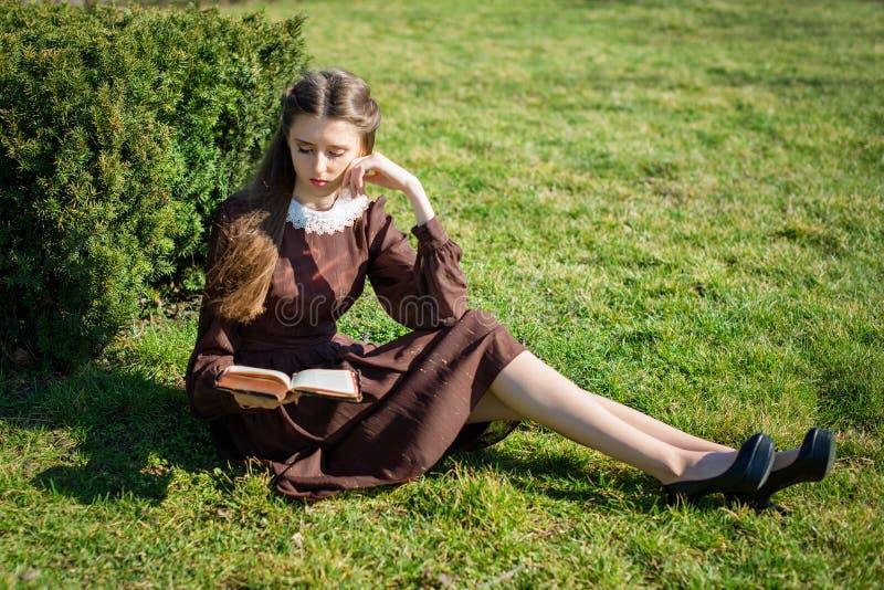 Ρομαντική νέα γυναίκα που διαβάζει ένα βιβλίο στη συνεδρίαση κήπων στη χλόη Χαλαρώστε την υπαίθρια χρονική έννοια στοκ φωτογραφία με δικαίωμα ελεύθερης χρήσης