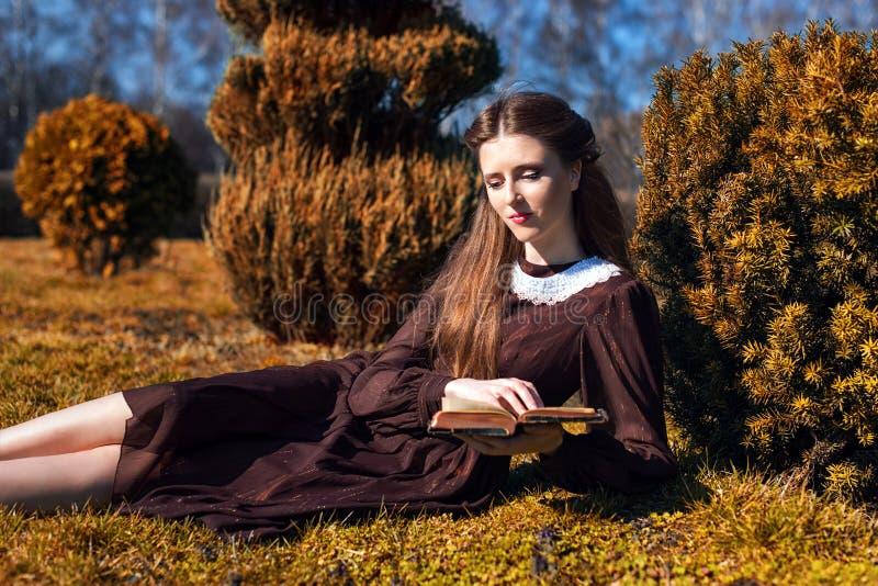 Ρομαντική νέα γυναίκα που διαβάζει ένα βιβλίο στη συνεδρίαση κήπων στη χλόη Χαλαρώστε την υπαίθρια χρονική έννοια στοκ φωτογραφία