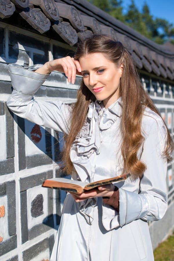 Ρομαντική νέα γυναίκα που διαβάζει ένα βιβλίο στον κήπο Χαλαρώστε την υπαίθρια χρονική έννοια στοκ φωτογραφία