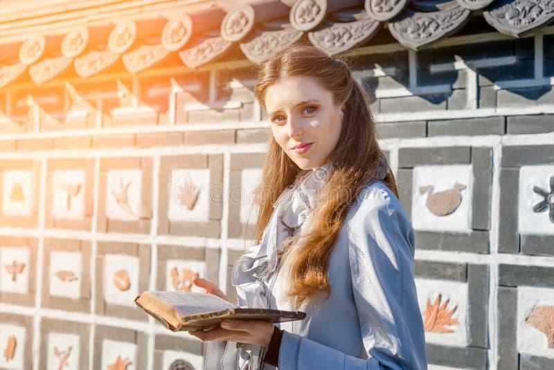 Ρομαντική νέα γυναίκα που διαβάζει ένα βιβλίο στον κήπο Χαλαρώστε την υπαίθρια χρονική έννοια στοκ εικόνες