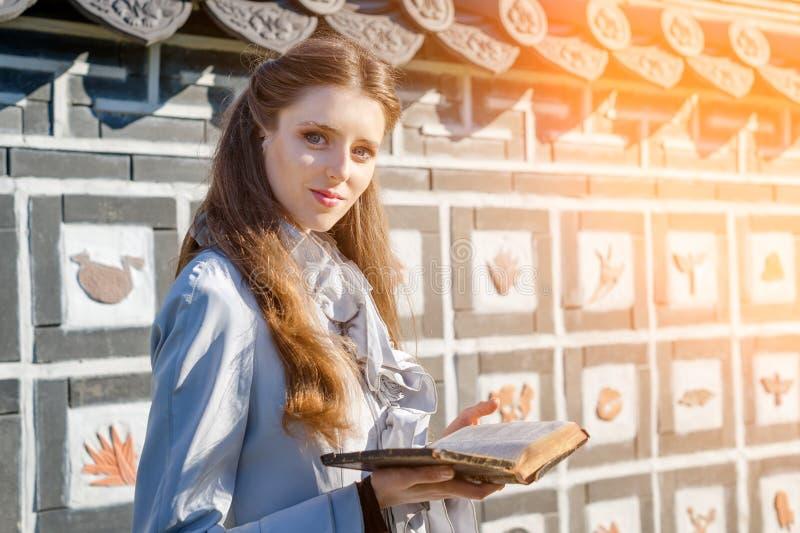 Ρομαντική νέα γυναίκα που διαβάζει ένα βιβλίο στον κήπο Χαλαρώστε την υπαίθρια χρονική έννοια στοκ εικόνες με δικαίωμα ελεύθερης χρήσης