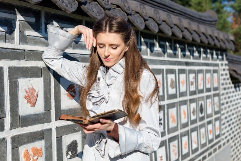 Ρομαντική νέα γυναίκα που διαβάζει ένα βιβλίο στον κήπο Χαλαρώστε την υπαίθρια χρονική έννοια στοκ φωτογραφία με δικαίωμα ελεύθερης χρήσης