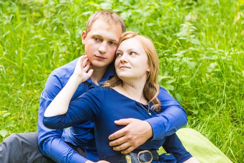 Ρομαντική νέα ερωτευμένη χαλάρωση ζευγών υπαίθρια στο πάρκο στοκ εικόνες