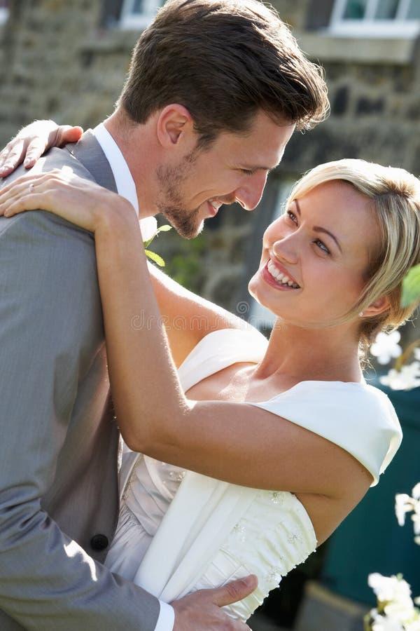 Ρομαντικοί νύφη και νεόνυμφος που αγκαλιάζουν υπαίθρια στοκ εικόνα