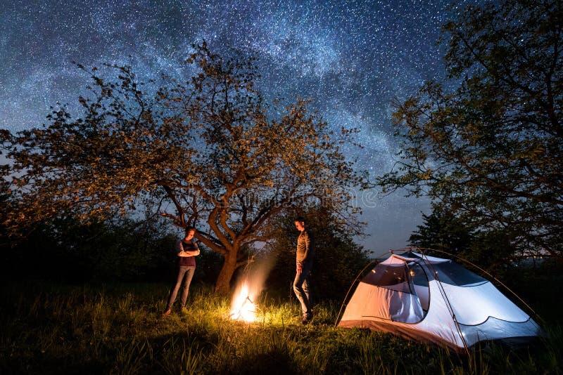 Ρομαντικοί τουρίστες ζευγών που στέκονται σε μια πυρά προσκόπων κοντά στη σκηνή κάτω από τα δέντρα και το σύνολο νυχτερινού ουραν στοκ φωτογραφίες