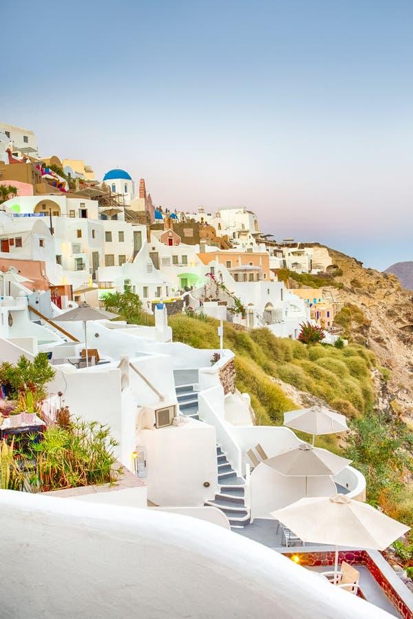 Ρομαντικός προορισμός Γραφική εικονική παράσταση πόλης Oia του χωριού στο νησί Santorini με Caldera τα βουνά στο υπόβαθρο στοκ εικόνα με δικαίωμα ελεύθερης χρήσης