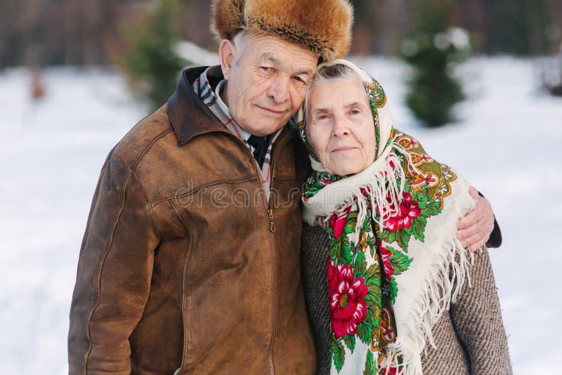 Ρομαντικό ανώτερο ζεύγος walkink στο πάρκο στο χειμώνα για πάντα αγάπη στοκ εικόνα