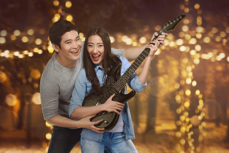 Ρομαντικό ασιατικό ζεύγος των εραστών που παίζουν την κιθάρα στοκ εικόνα