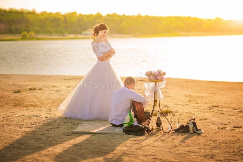 Ρομαντικό γαμήλιο ζεύγος στο ηλιοβασίλεμα στην ακτή με μια κιθάρα Η νύφη και ο νεόνυμφος κοντά στην ακτή σε μια παραλία ηλιοβασιλ στοκ εικόνες με δικαίωμα ελεύθερης χρήσης