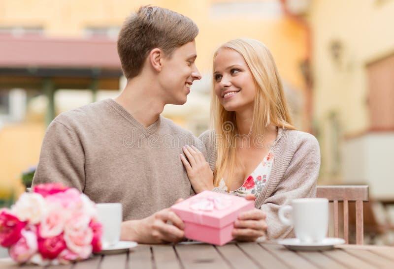 Ρομαντικό ευτυχές ζεύγος με το δώρο στον καφέ στοκ εικόνες