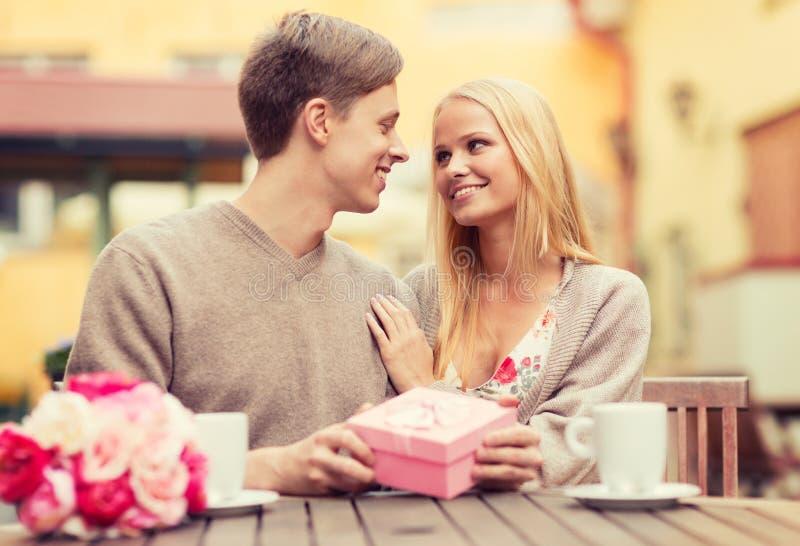 Ρομαντικό ευτυχές ζεύγος με το δώρο στον καφέ στοκ εικόνες με δικαίωμα ελεύθερης χρήσης