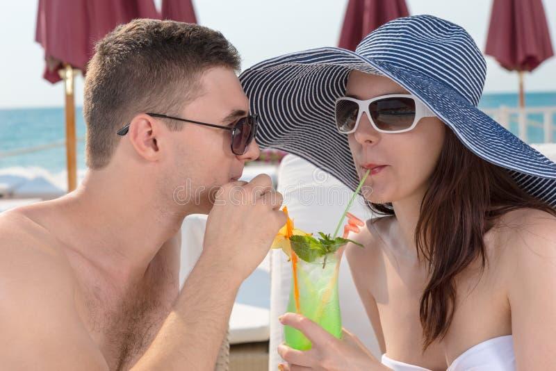 Ρομαντικό ζεύγος που μοιράζεται ένα τροπικό κοκτέιλ στοκ εικόνες