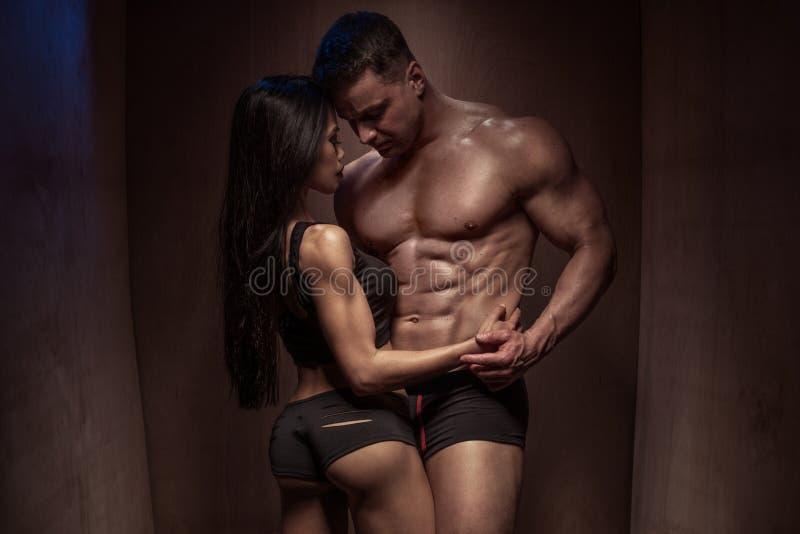 Ρομαντικό ζεύγος Bodybuilding ενάντια στον ξύλινο τοίχο στοκ εικόνα με δικαίωμα ελεύθερης χρήσης