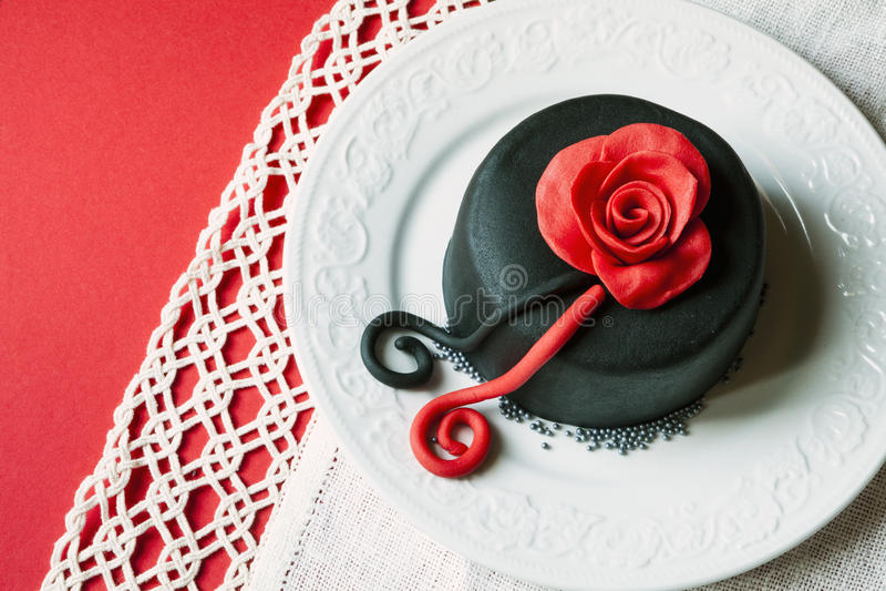 Ρομαντικό κέικ σε ένα πιάτο με τις διακοσμήσεις Αυξήθηκε ανωτέρω Κόκκινη ανασκόπηση στοκ φωτογραφία
