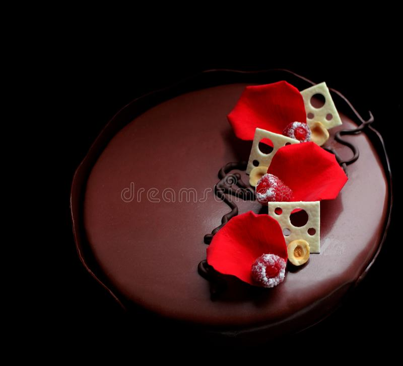 Ρομαντικό κέικ σμέουρων σοκολάτας με τα ροδαλά πέταλα, τις άσπρες διακοσμήσεις σοκολάτας και τα φρέσκα μούρα στο μαύρο υπόβαθρο στοκ φωτογραφίες με δικαίωμα ελεύθερης χρήσης