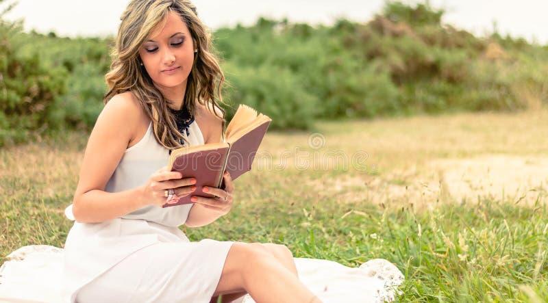 Ρομαντικό κορίτσι που διαβάζει μια συνεδρίαση βιβλίων υπαίθρια στοκ εικόνες