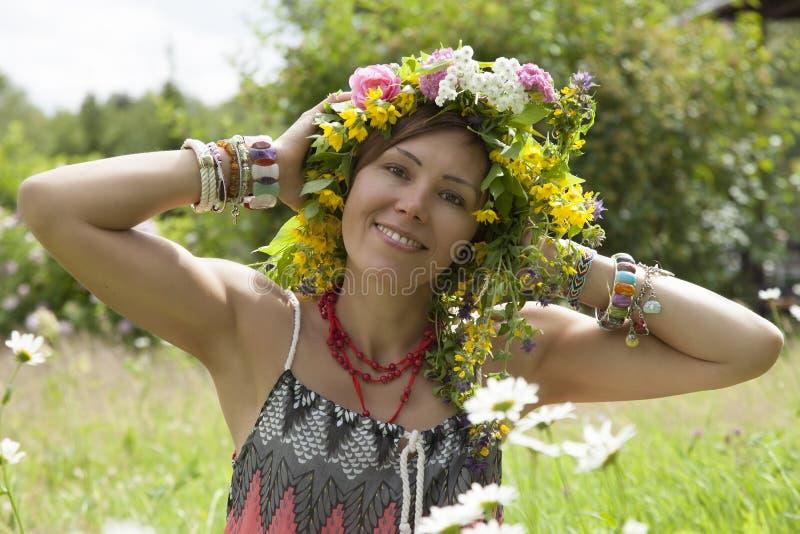 Ρομαντικό κορίτσι σε ένα στεφάνι των άγριων λουλουδιών στοκ εικόνα με δικαίωμα ελεύθερης χρήσης