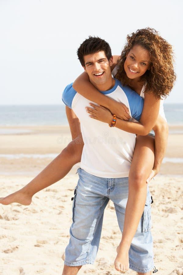 Ρομαντικό νέο ζεύγος που έχει τη διασκέδαση στην παραλία στοκ εικόνα