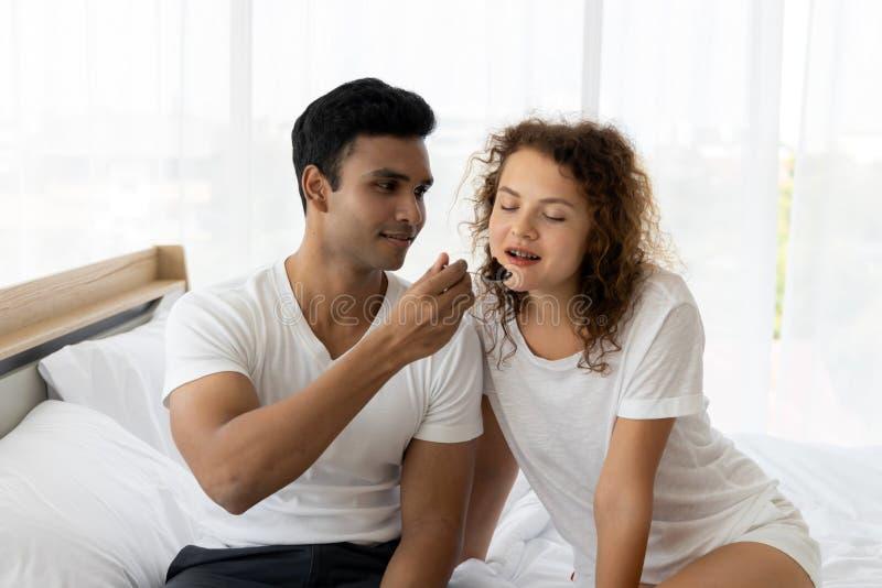 Ρομαντικό νέο ζεύγος που απολαμβάνει το κέικ μαζί στο κρεβάτι στην κρεβατοκάμαρα στοκ φωτογραφία με δικαίωμα ελεύθερης χρήσης