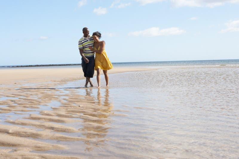 Ρομαντικό νέο ζεύγος που περπατά κατά μήκος της ακτής στοκ εικόνα