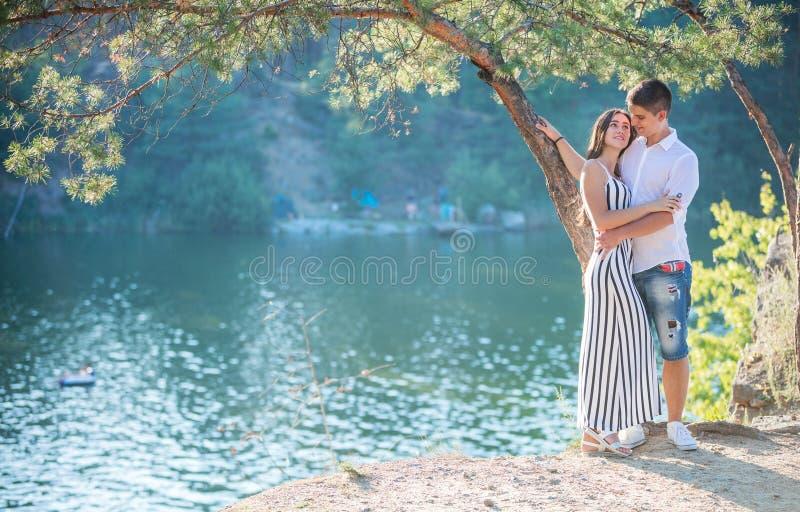 Ρομαντικό νέο ζεύγος που στέκεται στον απότομο βράχο πέρα από τον ποταμό στοκ φωτογραφία