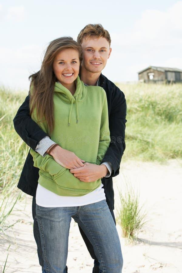 Ρομαντικό νέο ζεύγος που υπερασπίζεται τους αμμόλοφους στοκ εικόνες