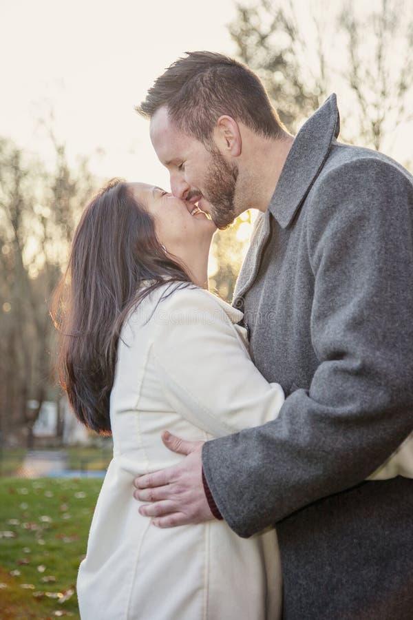 Ρομαντικό νέο ζεύγος που φιλά και που γελά έξω μια κρύα ημέρα πτώσης στοκ φωτογραφία με δικαίωμα ελεύθερης χρήσης