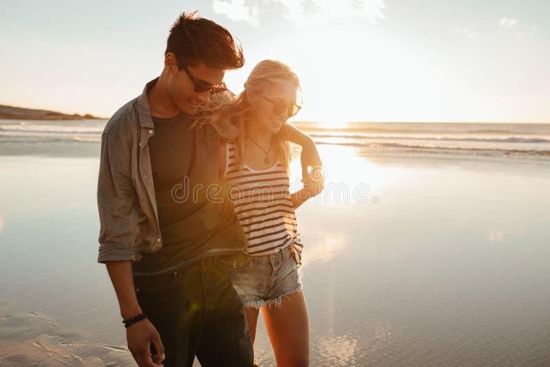 Ρομαντικό νέο ζεύγος στην παραλία κατά τη διάρκεια του ηλιοβασιλέματος στοκ εικόνες με δικαίωμα ελεύθερης χρήσης