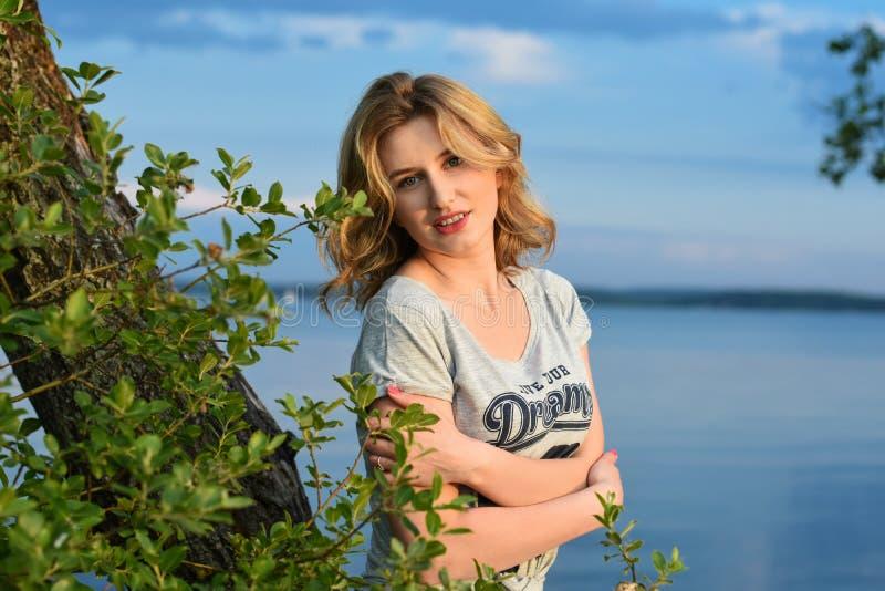 Ρομαντικό νέο κορίτσι στον ήλιο στο υπόβαθρο της ακτής του νερού λιμνών το βράδυ στοκ εικόνες