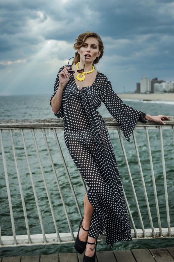 Ρομαντικό πορτρέτο της νέας γυναίκας που φορά το γραπτό φόρεμα στην αποβάθρα στοκ εικόνες