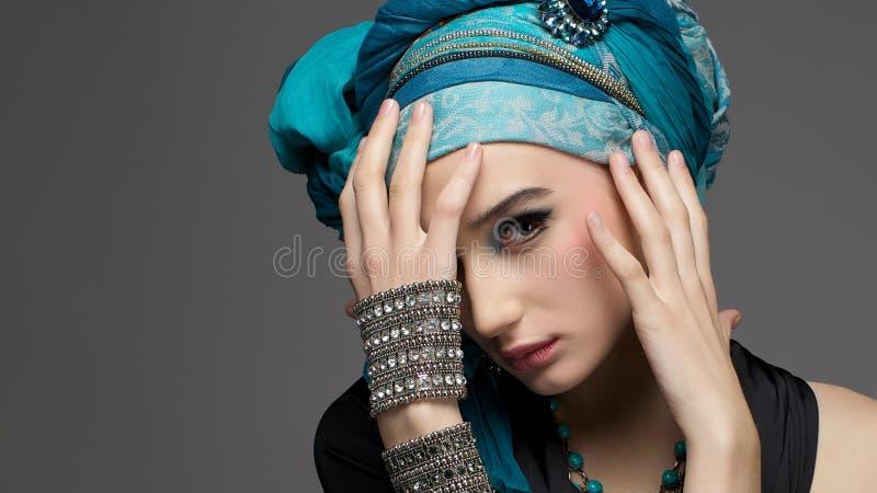 Ρομαντικό πορτρέτο της νέας γυναίκας σε ένα τυρκουάζ τουρμπάνι με το jewe στοκ φωτογραφίες