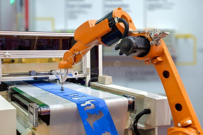 Ρομπότ για να πιάσει ένα κομμάτι προς κατεργασία από τη μηχανή στοκ εικόνα