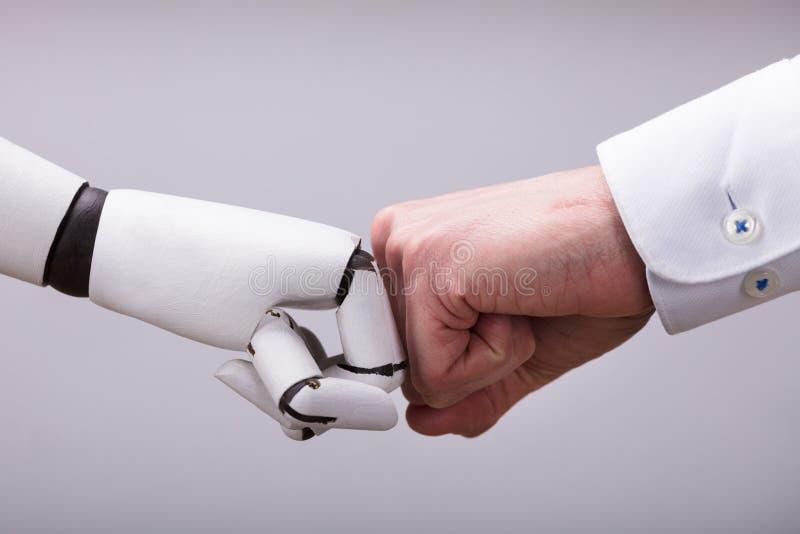 Ρομπότ και ανθρώπινο χέρι που κάνουν την πρόσκρουση πυγμών στοκ εικόνες