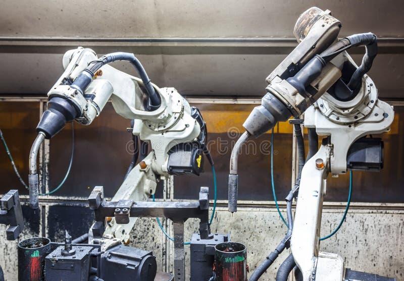 Ρομπότ που ενώνουν στενά την ομάδα στα αυτοκίνητα μέρη στοκ εικόνες
