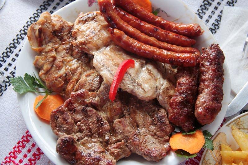 Ρουμανικό μικτό ψημένο στη σχάρα πιάτο με το βόειο κρέας, το χοιρινό κρέας, το κοτόπουλο και τα παραδοσιακά λεπτά λουκάνικα στοκ φωτογραφία με δικαίωμα ελεύθερης χρήσης